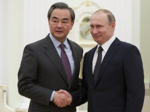 Russian President Vladimir Putin, right, shakes hands with Chinese Foreign Minister Wang Yi during their meeting in Moscow, Russia, Friday, March 11, 2016. The foreign ministers of China and Russia are opposing the possible deployment of an advanced American missile-defense system in South Korea. (AP Photo/Alexander Zemlianichenko, Pool)